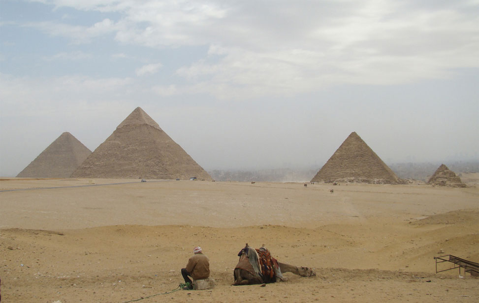 local man resting with camel near Giza Pyramids
