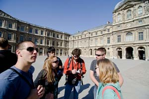 students gathered in front of the Louvre in Paris